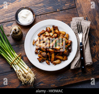 Fried potatoes roasted with Porcini wild mushrooms on white plate and green onions on wooden table background - Stock Photo