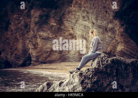 Pensive lonely young woman traveler relaxing on a big cliff stone on the beach looking at wild mountain scenery - Stock Photo