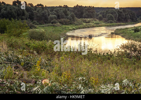 Beautiful countryside landscape with boat floating on river during sunrise in early morning - Stock Photo