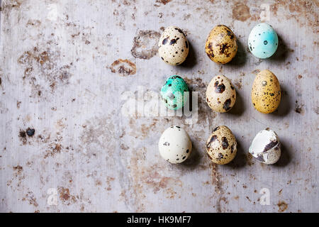 Decor whole and broken colorful Easter quail eggs standing in row rusty metaltexture background. Top view with copy - Stock Photo