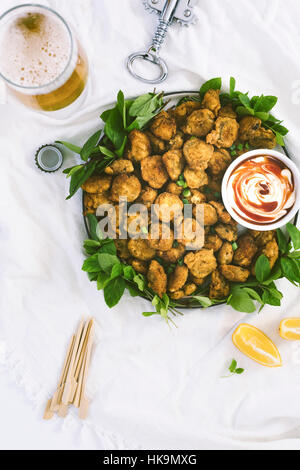 Fried pickles accompanied by a ketchup and mayonnaise sauce and a glass of beer photographed from top view. - Stock Photo