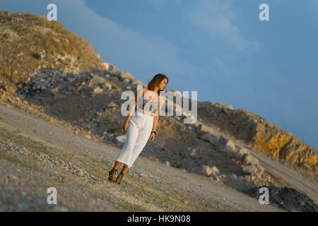 Isolated outdoors looking away attractive White pants bra-top busty shapely body angled shot wilderness alone single - Stock Photo
