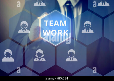Businessman touching 'TEAM WORK' word on virtual screen with people from different occupations - Stock Photo