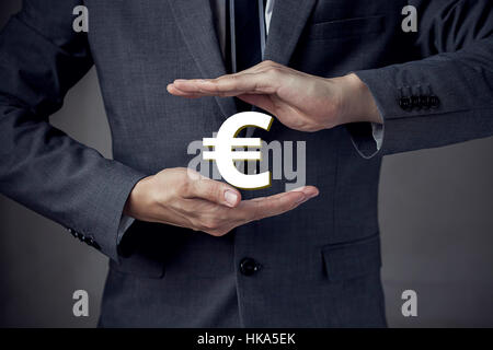 3D Euro currency sign in between two hands of businessman - Stock Photo