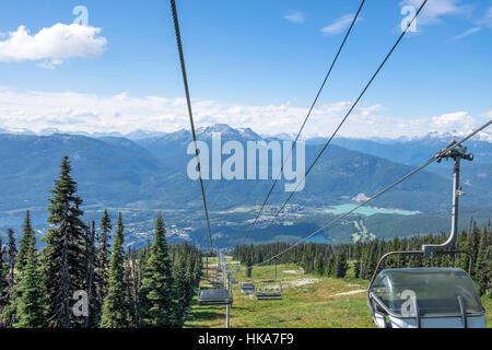 Stunning views of the distant mountains and valley below can been seen traveling down the chair lift on Blackcomb - Stock Photo