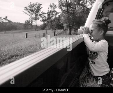 Little girl looks through binoculars. - Stock Photo