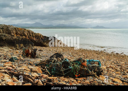 Discarded plastics, lobster pots, fishing nets on a North Wales beach - Stock Photo