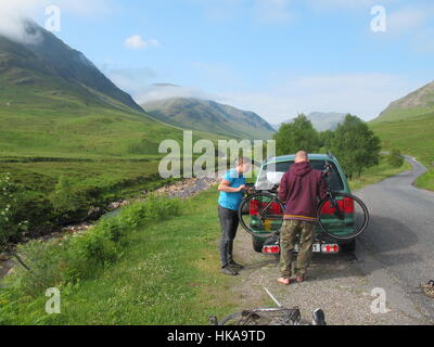 Female cyclist on Glen Etive single track road Scotland uk - Stock Photo
