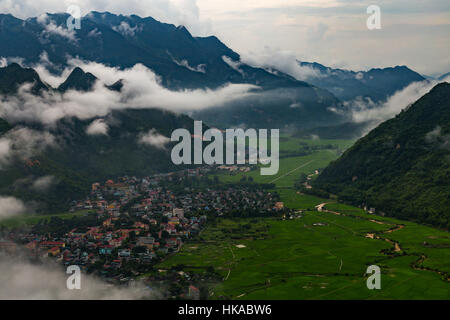 Green valley with a Vietnamese town and rice fields surrounded by mountains - Stock Photo