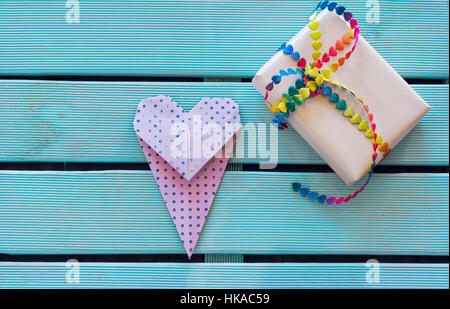 Overhead of handmade gift with vibrant bow tie and bookmark origami heart on blue wooden background and copy space. - Stock Photo