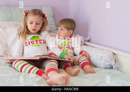 adorable brother and sister siblings reading story together storytime holidays matching pajamas christmas - Stock Photo