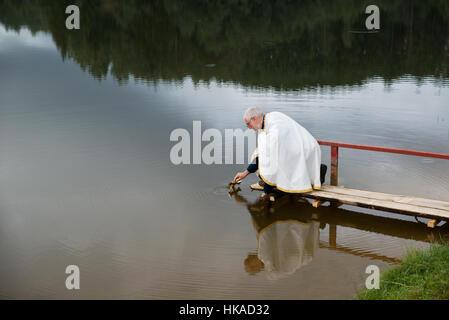 Immersing a cross during the ceremony before Transfiguration Day of Seto people, Obinitsa, Estonia - Stock Photo