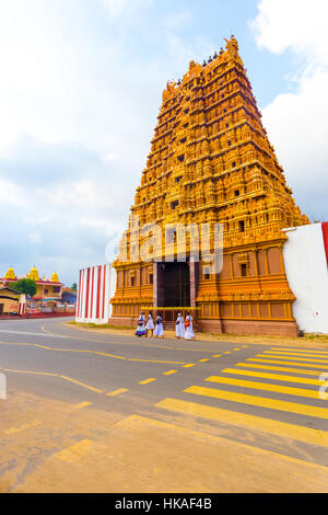 Sri Lankan people on the road in front of Golden Entrance gopuram tower, Swarna Vaasal, in Kandaswamy Kovil Temple - Stock Photo