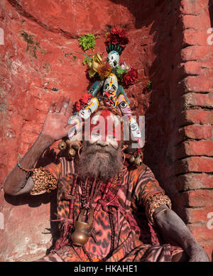 Holy man or sadhus at Pashupatinath Kathmandu Nepal. The mans face is painted red and white he has a headdress and - Stock Photo