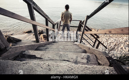 Young man stands on old wooden stairway going down to the sea coast. Vintage toned photo, old style photo filter - Stock Photo