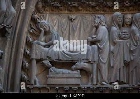 Nativity of Jesus. Detail of the Gothic tympanum from circa 1250 on the northern facade of the Notre-Dame Cathedral - Stock Photo