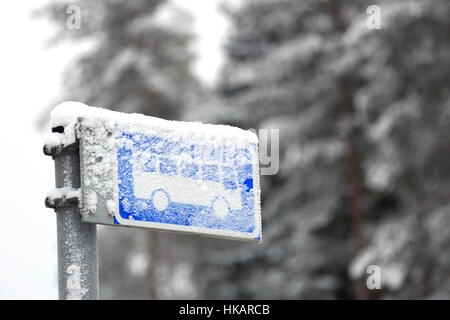 Frosty and snowy bus stop sign on a cold day in winter against grey blurred forest. - Stock Photo