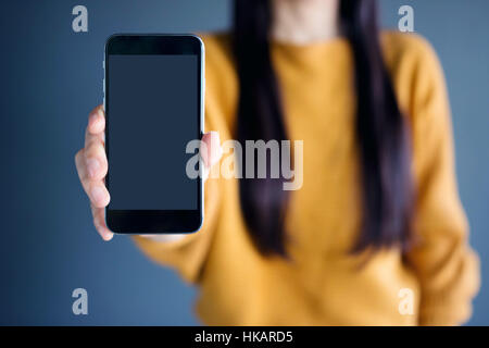 Smart Phone Mockup image with Long Black Hair Female Model holding and showing a mobile with blank screen - Stock Photo