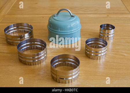 Set of traditional 5 five cookie biscuit cutters laid out on a wooden table in the kitchen with metal holder - Stock Photo