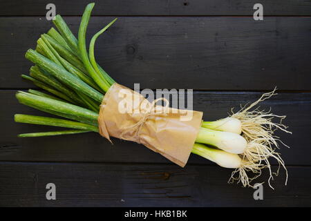 Raw food ingredients bouqet of spring onions on black boards. Top down. Flat lay. - Stock Photo