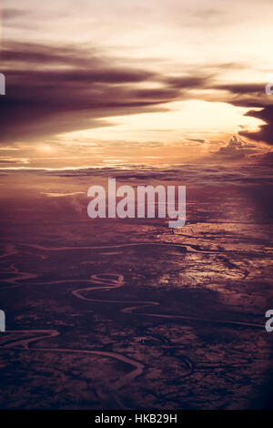 Dramatic sunset over the earth from the height in vintage style with epic sky. - Stock Photo