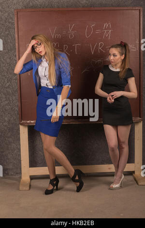Woman teacher in a daring outfit and embarrassed the student in front of the old school board. - Stock Photo