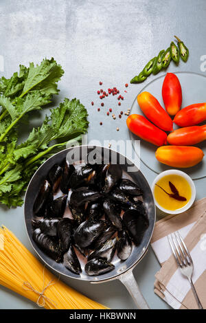mussels in a pan with the ingredients. recipe with spaghetti and tomato. - Stock Photo