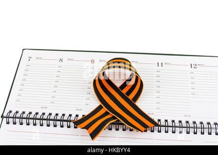 In an open diary sheet is St. George's ribbon in a bow - Stock Photo