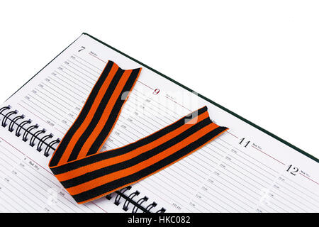In an open diary sheet is St. George's ribbon in the form of the letter V - Stock Photo
