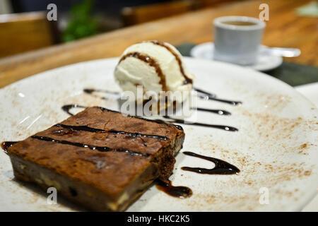 Brownie with vanilla ice cream and chocolate syrup - Stock Photo