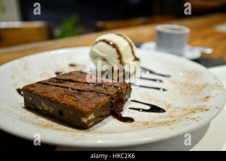 Brownie with vanilla ice cream and chocolate syrup - Stock Photo