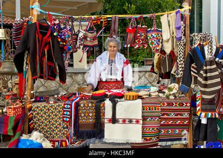 Lady in traditional clothes selling traditional croatian clothes on Biograd street fair, Dalmatia, Croatia - Stock Photo