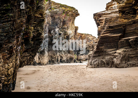 Sandstone cliff on a sandy beach in Atlantic ocean Spain. Blue skies with clouds over tropical beach with sand in - Stock Photo