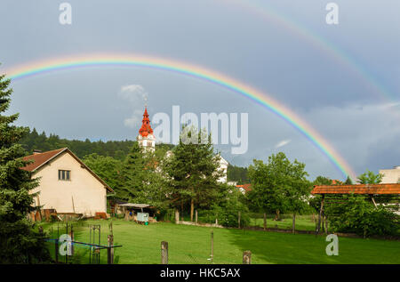 Double rainbow over a church in a cloudy village. Traditional farm with church in a village and double rainbow over - Stock Photo