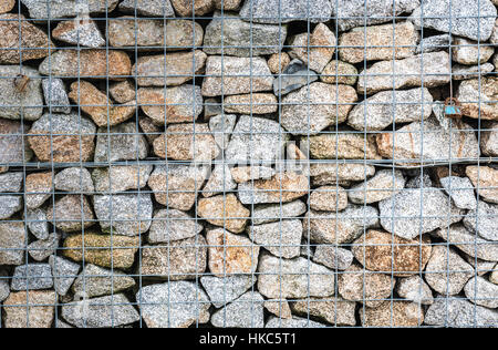 Wire Gabion Rock Fence. Metal Cage filled with rocks. Texture background of rock fence with cage. - Stock Photo