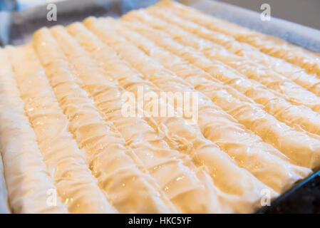 Baked homemade traditional Balkan, Bosnian, Greek, Turkish or Serbian dish burek. Domestic pastries on backing tray - Stock Photo