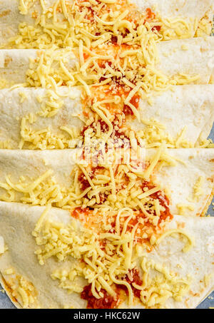 Homemade traditional Mexican food burrito, fajitas, Quesadillas, Enchiladas or tacos with cheddar cheese on a backing - Stock Photo