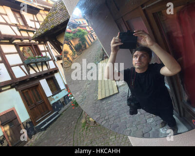 Photographer Vova Pomortzeff uses a smartphone to make a selfie using a convex mirror in Eguisheim, Alsace, France. - Stock Photo