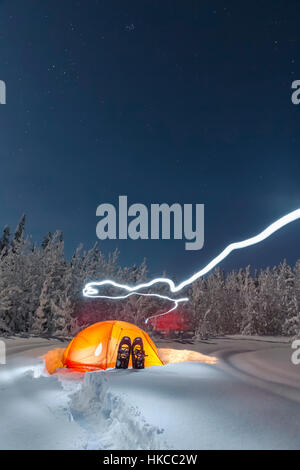 Lit tent near an evergreen and snow covered forest, Gakona, Southcentral Alaska, Winter - Stock Photo