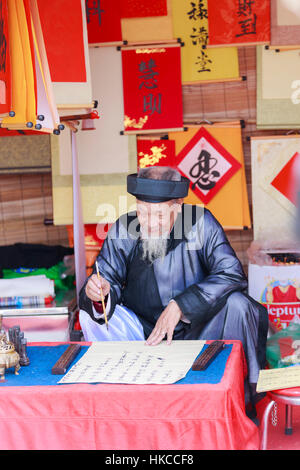 A scholar writes Chinese calligraphy characters at Temple of Literature on January 26,2017 - Stock Photo