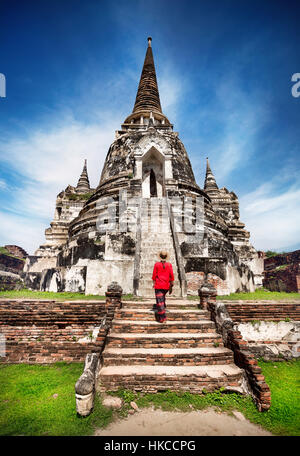 Tourist Woman in red costume looking at ancient ruined stupa in Ayutthaya Historical Park, Thailand - Stock Photo