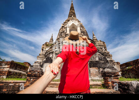 Tourist Woman in red shirt holding her husband by hand and going to ancient stupa in Ayutthaya Historical Park, - Stock Photo