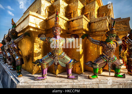 Demon golden statues support pyramid at Wat Phra Kaew in Grand Palace in Bangkok, Thailand - Stock Photo