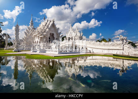 Wat Rong Khun The White Temple and pond with fish, in Chiang Rai, Thailand - Stock Photo
