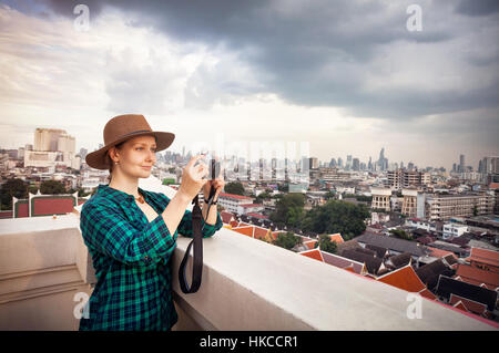 Tourist woman taking pictures with retro style camera at Bangkok City panorama with skyscrapers of business district - Stock Photo