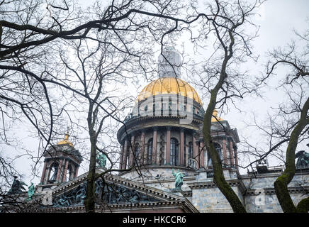 Famous Isaac's Cathedral and old oak trees at dramatic gray sky in St. Petersburg, Russia - Stock Photo