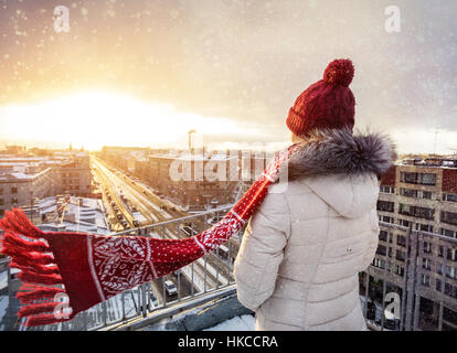 Woman in Christmas Hat and red scarf on the roof at snow fall in Saint Petersburg, Russia
