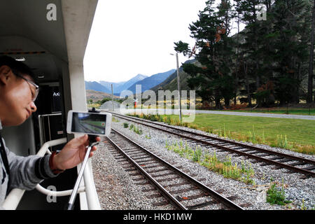 Recording video using smart phone  from inside the open coach of TranzAlpine train from Christchurch To Greymouth - Stock Photo