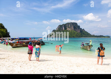KRABI, THAILAND - DECEMBER 19 2015: Two Chinese tourists take a photo of their friend in front of an island near - Stock Photo