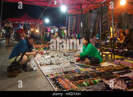 LUANG PRABANG, LAOS - MAY 15 2015: A tourist looks for souvenir in Luang Prabang night market, a prime travel destination - Stock Photo